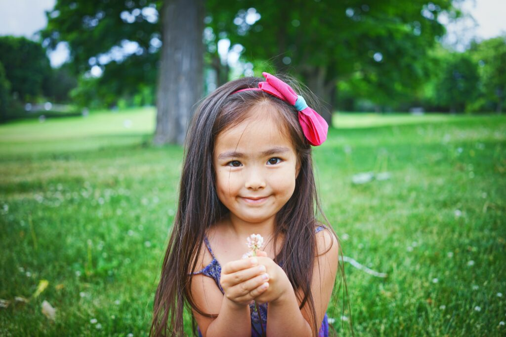 Smiling Little Girl with Wildflowers